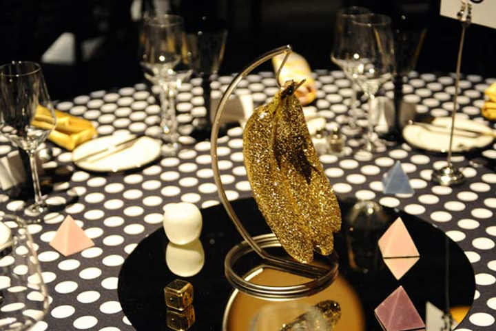 For the Redcat gala, Two Serious Ladies designed the artful decor that included a constellation of golden, glowing orbs hanging above the main room and centerpieces made of glittering bananas, toy horseshoes, marble pyramids, and golden dice.