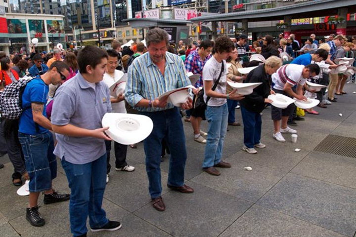 In Dundas Square, visitors looked eagerly into one of 200 white cowboy hats for the winning red envelope, which would give them a chance to experience the Calgary Stampede's centennial.