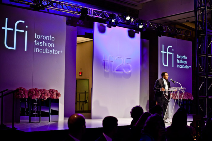 A three-dimensional T.F.I. logo marked the centre of the multipaneled runway backdrop in the V.I.P. area. Pink hydrangeas bordered the stage.