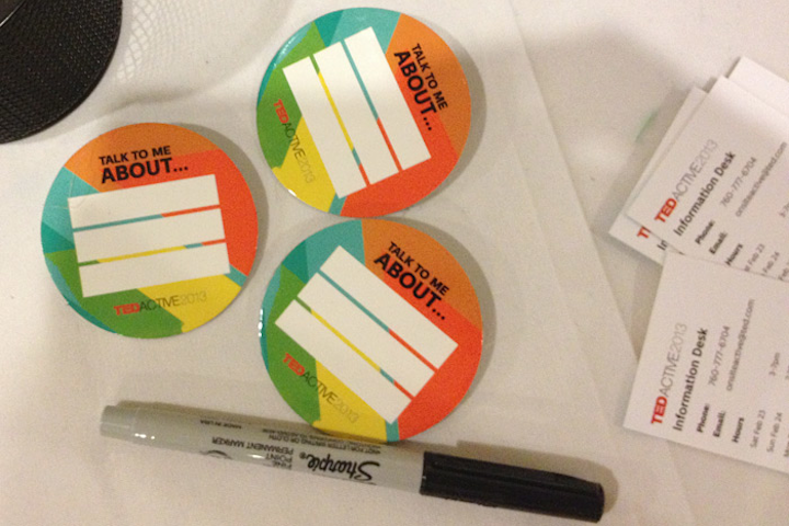 At TEDActive in Palm Springs, buttons with blank fields labeled 'Talk to Me About ... ' invited guests to write a short list of topics they love or are knowledgeable about, to encourage meaningful mingling.