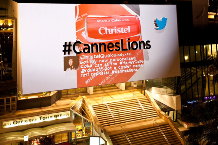 During the day, the billboard above the venue entrance simply displayed the event's hashtag in black letters. As the sun went down each night, a projector mounted on a roof across the street added a 3-D display of tweets and photos that used the official hashtag.