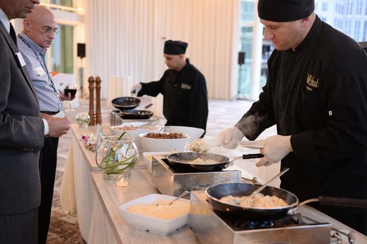 An action station, such as Puff 'n Stuff Catering's risotto bar, allows guests to customize their food and watch it being prepared.