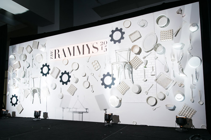 Design Foundry used silver cooking utensils along with pots, pans, and platters to adorn the backdrop for the stage.