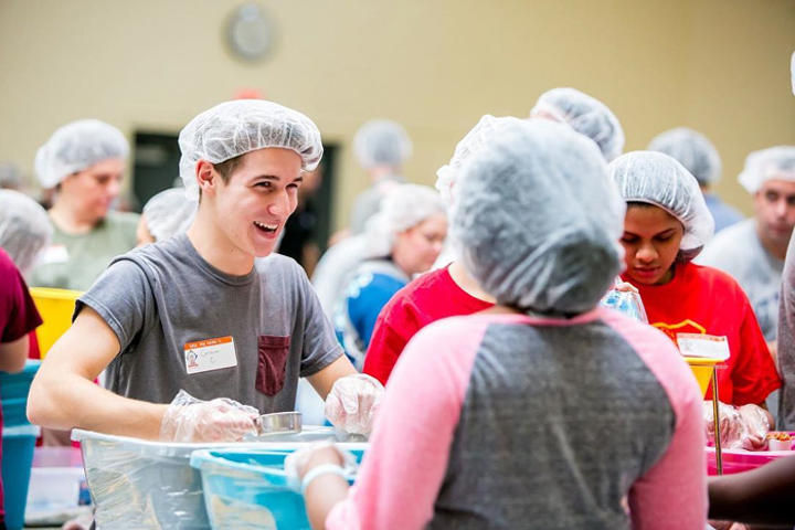 Feeding Children Everywhere assembles groups to package healthy meals for children in need.