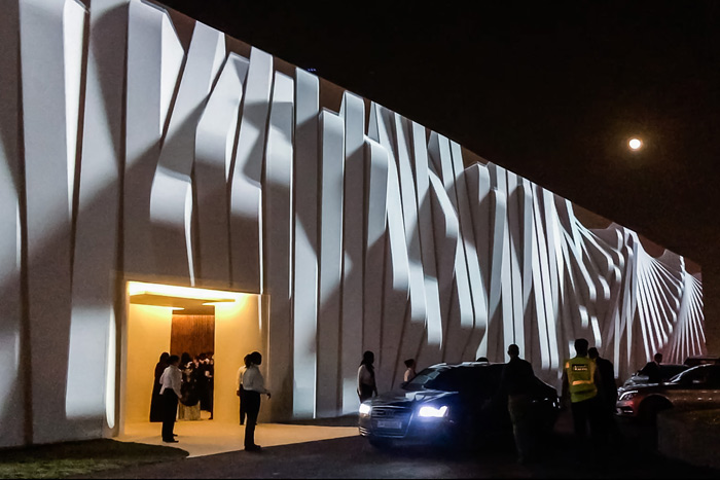 Images from 18 projectors merged together to create one seamless image on a 30- by 360-foot fabric-covered wall. An entrance in the middle led guests into the tent that housed the wedding party.