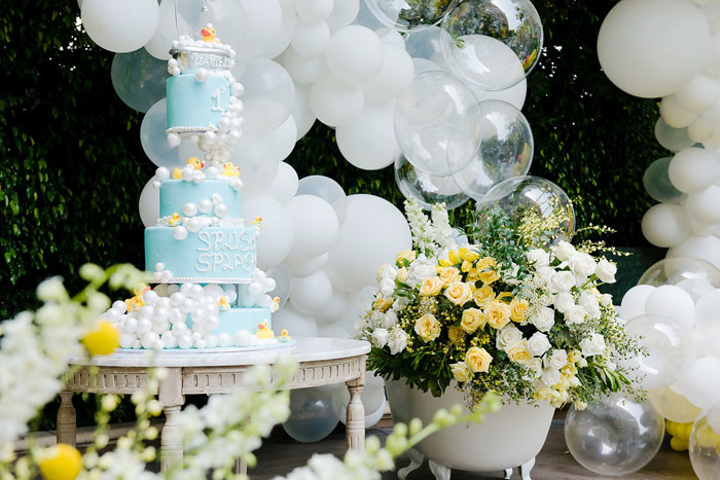 Next to the bathtub was an eye-catching blue cake, which was topped with more bubbles, rubber ducks, and the words 'splish splash.' On the top was a rubber duck taking a bath.