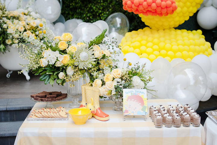 At another dessert table, rain boots and the book 'Splish Splash Baby' served as on-theme props.