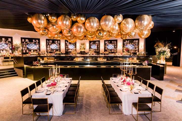 The gold details continued with a grouping of 'golden globes' that hung above the bar area. Props and decor were provided by Studio D Decor, Revelry, Mr. Foam & Scenic, and Theoni. Images by Lighting handled the lighting.