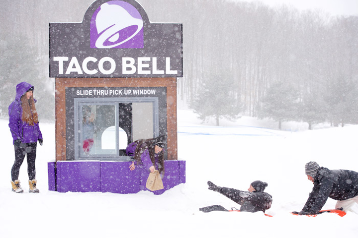 From a 'slide-thru' window, Taco Bell ambassadors handed out Cheetos Crunchwrap Sliders to consumers who tubed down a hill.