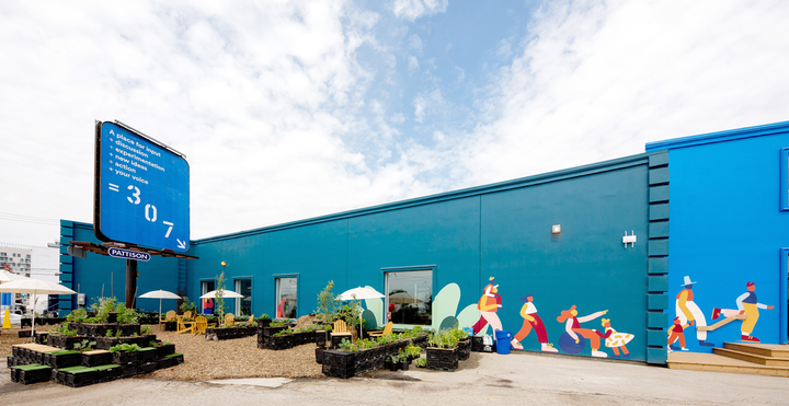 """The project's headquarters and community space, dubbed """"307,"""" features an outdoor area for visitors and an exterior mural designed by Montréal-based illustrator Cécile Gariépy."""