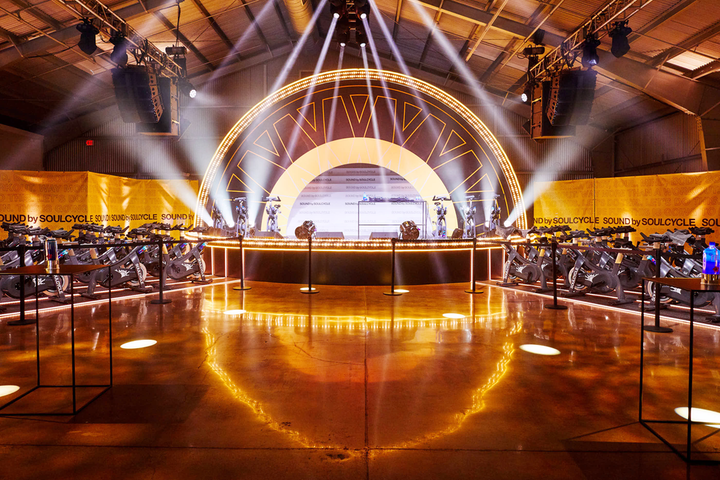 """For the debut Sound by SoulCycle event in Los Angeles, """"the creative concept for the concert centered around 'sound as sanctuary.' Guests entered the hangar-esque, nightclub-like space through a wheel-like portal, reducing the guest experience to a meditative tunnel where affirmations were delivered via sound-isolation pods…. At the center was a studio-stage hybrid, stylized like a bent-wheel where enthusiasts powered the light stage with their energy."""""""