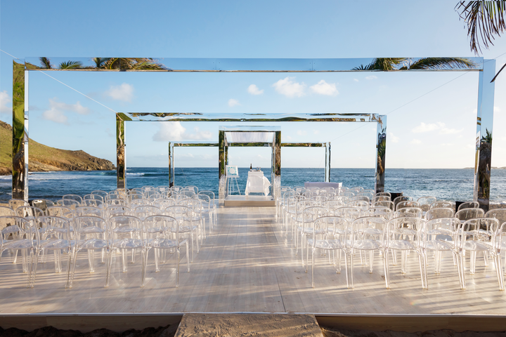 """We cheated perspective with an inwards-moving platform and a series of reflective arches that shrank progressively towards the horizon, making guests feel as if they were moving into the sea ahead. The contemporary chuppah was simple and sleek, taking advantage of the gorgeous St. Barth's scenery by reflecting the beach, and the use of clear chairs kept the ceremony open, airy, and light.' Pictured: Private wedding in St. Barth's"