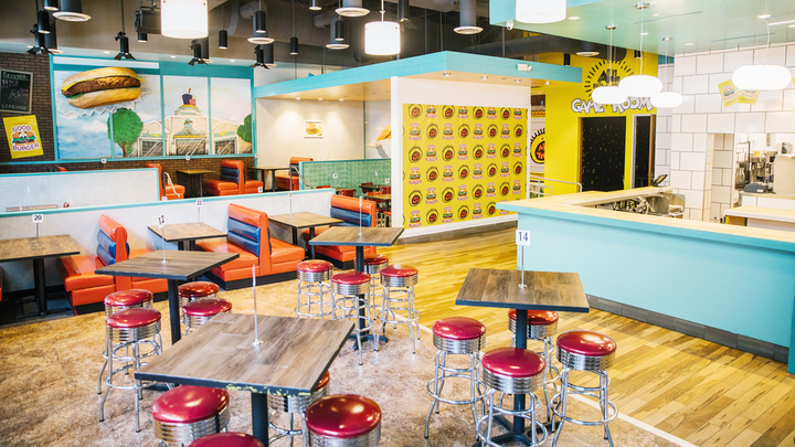To promote the return of Nickelodeon's All That sketch comedy series, the network opened a pop-up dining experience this week that's inspired by the old Good Burger sketch starring Kenan Thompson and Kel Mitchell. Open through the end of 2019, the nostalgic space—created by the same team behind the recent 'Saved by the Max' pop-up—serves food from local chef Alvin Cailan, founder of Eggslut. The pop-up, which was designed by multidisciplinary artist Floyd A. Davis IV, also has photo moments, games, merchandise, and, as fans can appreciate, plenty of orange soda.
