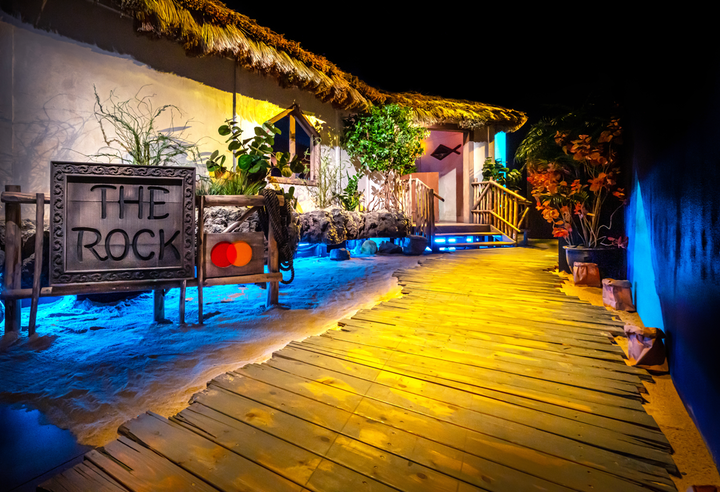 Mastercard brought on Adirondack Studios to design a replica of the Rock in Zanzibar. Guests enter the venue on a boardwalk over sand, surrounded by tropical plants, recalling the original location of the restaurant, which is owned by Nigel Firman.