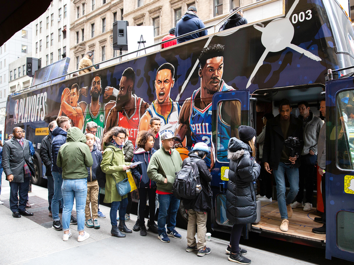 "For the N.B.A. Playoffs in April, the league activated two pop-up buses in New York and Los Angeles for fans. The activations featured a Beats listening station, an NBA 2K gaming lounge, and a Larry O'Brien Trophy photo booth, as well as store offers and giveaways. The buses were wrapped in ""Heroes Wanted"" campaign imagery."
