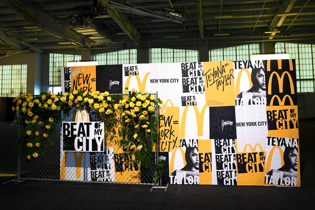 The New York event's step and repeat featured yellow roses draped on a piece of chain-link fence, backed by a sign wall displaying the name of the event and the headliner. Narrative is producing and designing the tour.