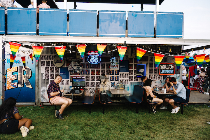 Bud Light brought its traveling Dive Bar activation to Governors Ball in New York for the first time in June. The back of the Bud Light Dive Bar activation featured imagery welcoming guests, along with dive bar-inspired decor and seating. The wall was plastered with vintage Bud Light ads and neon signs.