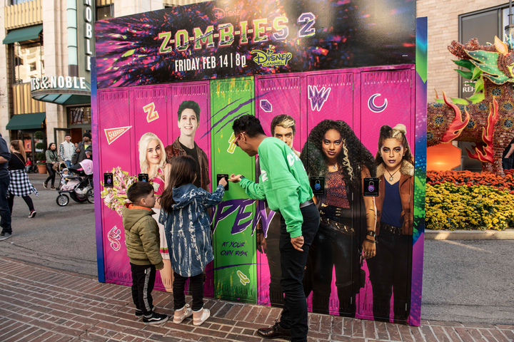 To promote the Disney Channel's new Zombies 2 film, the company worked with GDX Studios on a family-friendly stunt that placed lockers at various locations around the country. Passersby of all ages were encouraged to open the lockers, where zombie, werewolf, or cheerleader hands would give them a themed prize. In addition to the Grove in Los Angeles (pictured), the stunt traveled to San Diego; Raleigh, North Carolina; Louisville, Kentucky; Baltimore; Philadelphia; Orlando; and Miami; in all, some 10,000 gifts were distributed.