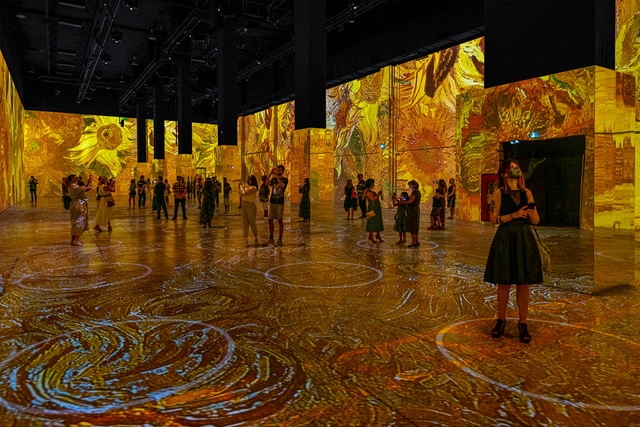 Images from famous paintings like 'Sunflowers' are projected on the walls and floor.