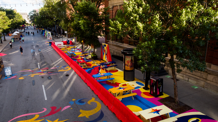 'Together Apart Street Art' is a large-scale outdoor art installation on Saint-Laurent Boulevard. The 140-foot-long mural uses shapes, lines, and vibrant contrasting colors to direct pedestrian flow and encourage social distancing.