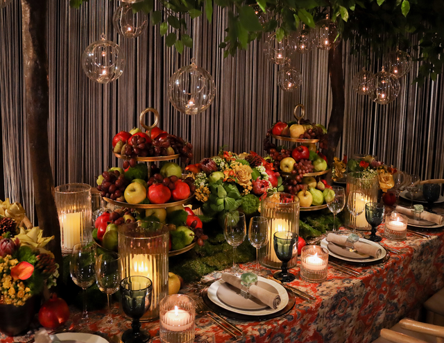Candles in hand-blown glass spheres cast a soft glow over the vibrant, fruit-filled table.